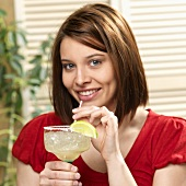 Woman Holding a Margarita with a Straw in a Salted Glass