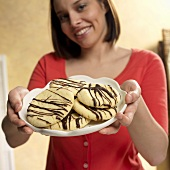 Woman Holding a Plate of Almond Cookies Drizzled with Chocolate