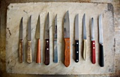 Various Steak Knives Lined Up in a Row, From Above
