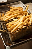 French Fries in Deep Fryer Baskets Over Frying Oil