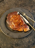 Rib Eye Steak on a Plate with a Fork and Knife