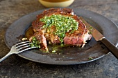 Rib Eye Steak Topped with Herb Sauce on a Plate, Sliced