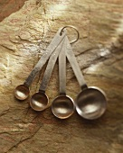 Set of Metal Measuring Spoons on Stone Surface