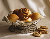 Baked Goods in a Wire Basket, Cinnamon Buns, Cookies Next to Basket