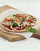 Ganze Gemüsepizza auf Papier am Schneidebrett