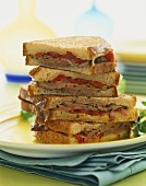 Four Grilled Panini Halves Stacked on a Plate