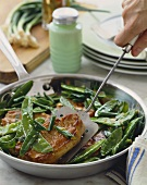 Boneless Pork Chops with Snow Peas in a Skillet, Removing Pork Chop with Spatula