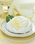 Lemon Meringue Tartlet on a Plate with Lemon Zest Garnish