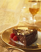 Slice of Chocolate Torte with Gold Decorations and Raspberries
