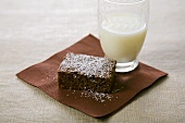 Brownie Topped with Powdered Sugar and a Glass of Milk