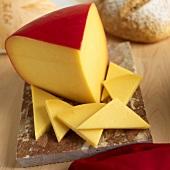 Eine Ecke Goudakäse in roter Wachshülle und ein paar Käsescheibchen