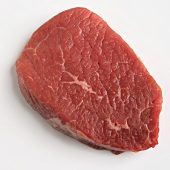 A beef steak on a white surface