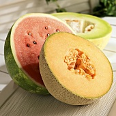 Three Melon Halves on a Picnic Table; Watermelon, Cantaloupe and Honeydew