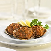 Three Stuffed Clams with Lemon Wedges and Parsley Garnish