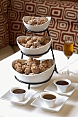Fried dough balls on tiered stand, with various sauces