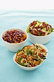 Three different vegetable salads in white dishes