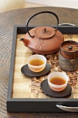 Asian teapot and two bowls of tea on tray