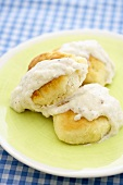Biscuits Topped with White Gravy on a Yellow Plate