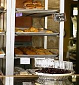 Brombeerpie auf Tisch vor Auslage in Bäckerei