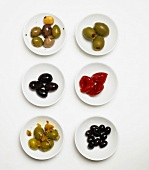 Various Olives & Chilies on White Plates
