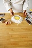 Nudelteig zubereiten: Eier im Mehlhaufen verrühren