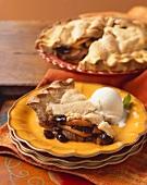 Slice of Apple Raisin Pie with a Scoop of Vanilla Ice Cream on Stacked Plates