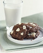 Chocolate White Chunk Cookies on a Plate with a Glass of Milk