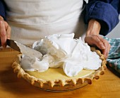 Baker Spreading Meringue On a Cream Pie