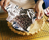 Baker Removing Dried Beans and Tinfoil From a Baked Pie Shell