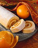 Rolled Orange Sponge Cake Sliced on a Platter