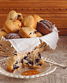 Blueberry Muffin Halved on a Plate; Basket of Assorted Muffins