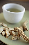 Dried Ginseng Root on a Plate with a Cup of Ginseng Tea