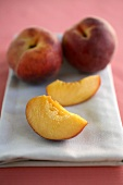 Two Peach Slices and Two Whole Peaches on a Folded Dish Cloth