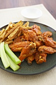 Buffalo Wings on a Plate with Celery Sticks and French Fries