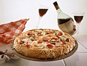 Whole Pizza with Pepperoni, Shrimp and Vegetables, Glasses and Bottle of Red Wine