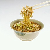 Chopsticks Removing Noodles and Vegetables From Soup Bowl, White Background