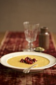 Bowl of Pumpkin Soup Topped with Chunky Cranberry Sauce