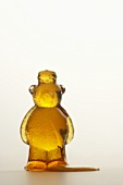 Honey Spilling From an Opened Honey Bear, White Background