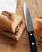 Turkey, Tomato and Lettuce Sandwich on a Baguette; Halved with Knife