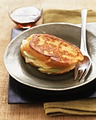 Apple and Cheese Stuffed French Toast on a Metal Plate; Maple Syrup