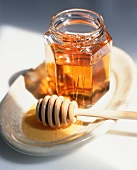 Honey Dipper and Opened Jar of Honey on a Dish