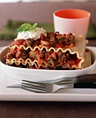 Serving of Ground Beef Lasagna in an Oval Dish; Fork and Knife