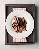 Four Slices of Steak with Mushroom Sauce on a White Plate; From Above