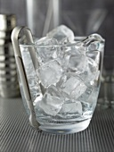 Ice cubes and ice tongs in a glass container