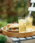 Tray on an Outdoor Chair with Glasses of Ice Tea and Sandwiches