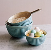 Three Blue Mixing Bowls; One with Colored Eggs, One with Flour
