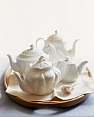 Assorted White Teapots on a Tray with a Tea Strainer