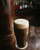 Glass of Dark Beer with Foam on a Bar
