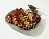 Roast Beef in Scheiben mit Bratensauce und Röstgemüse