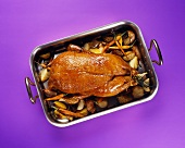 Whole Roast Duck on a Bed of Vegetables in a Roasting Pan